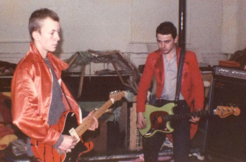 Sage & Gaz wearing red jackets from Mid-Pennine Arts dressing up box.
